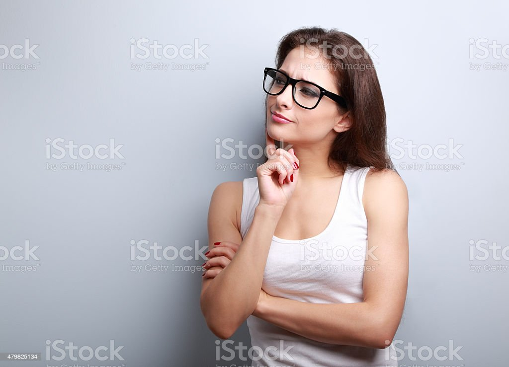 Thinking serious young woman in glasses looking on empty copy stock photo