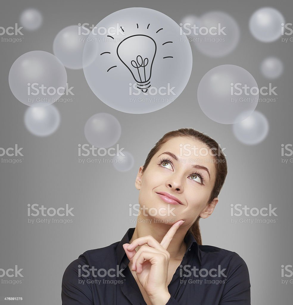 Thinking smiling woman looking on many bubbles with idea bulb royalty-free stock photo
