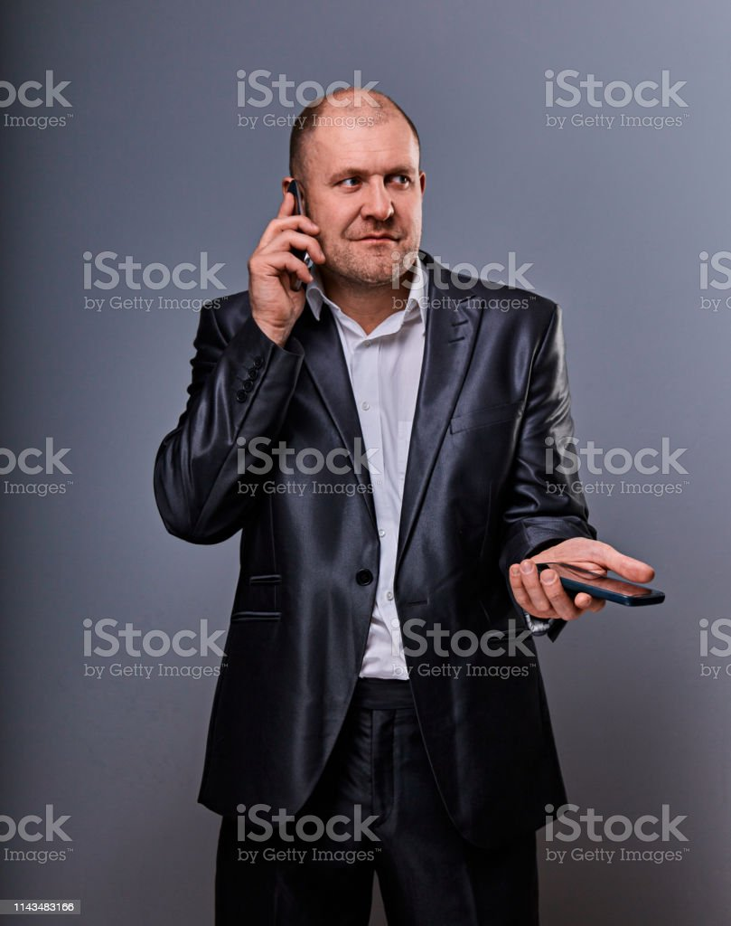 Thinking stressed angry doubt business man talking on mobile phone very emotional in office suit on grey background. Closeup royalty-free stock photo