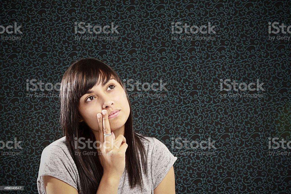 Thinking things over. Pensively pretty brunette looks up sideways royalty-free stock photo