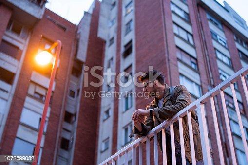 Young man, exploring city and using smartphone at night