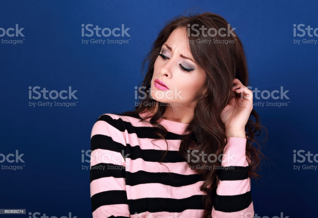 Thinking unhappy angry makeup with long curly hair style woman looking down and scratching the head blue empty copy space background stock photo