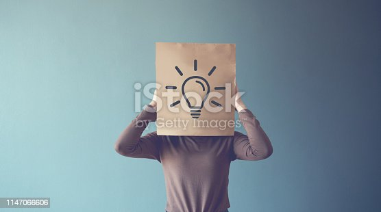 istock Thinking woman covering his face with idea light bulb, copy space. 1147066606