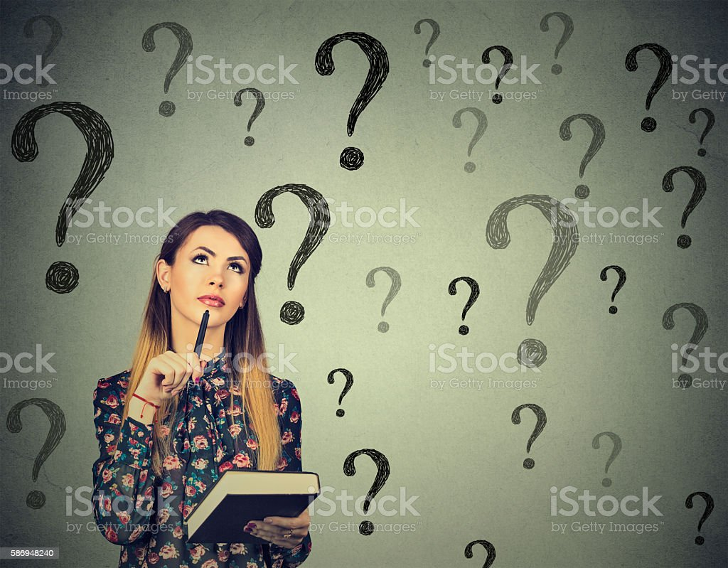 Thinking woman looking up at many questions mark stock photo