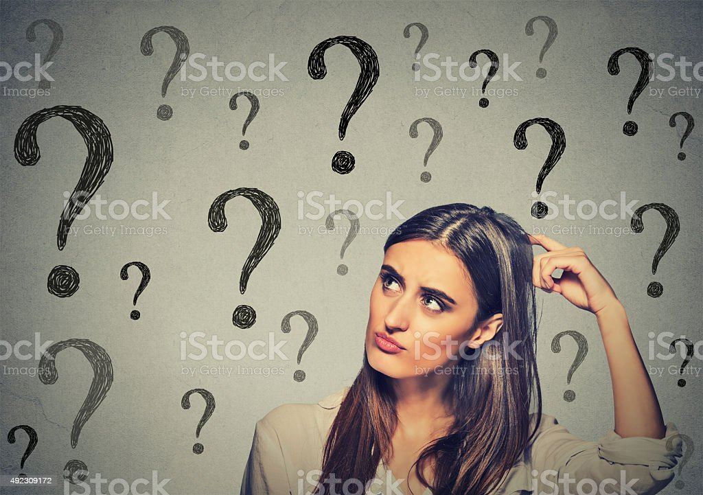 thinking woman scratching her head looking up at question marks stock photo