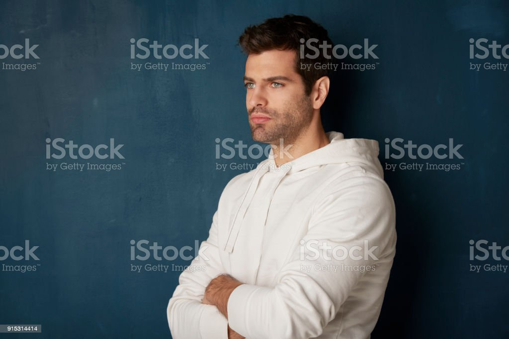 Thinking youn man standing with arms crossed stock photo