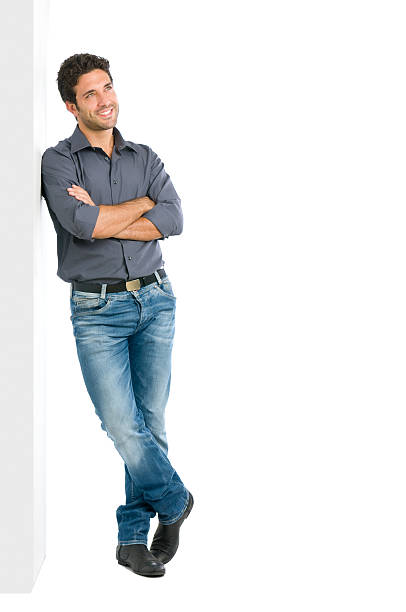 Thinking young man full length Happy smiling young man leaning against white wall with dreaming and pensive expression, copy space on the right. leaning stock pictures, royalty-free photos & images