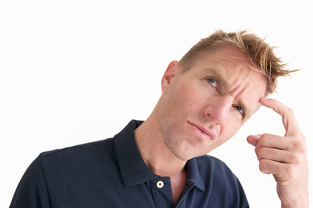 Thinking Young Man Scratching Head Looking Up White Background stock photo