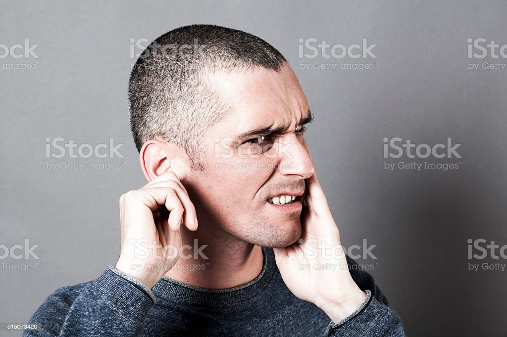 thinking young man suffering from earache or toothache stock photo