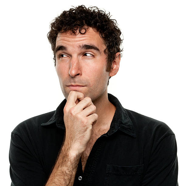 Thinking Young Man With Hand On Chin Looking Away stock photo