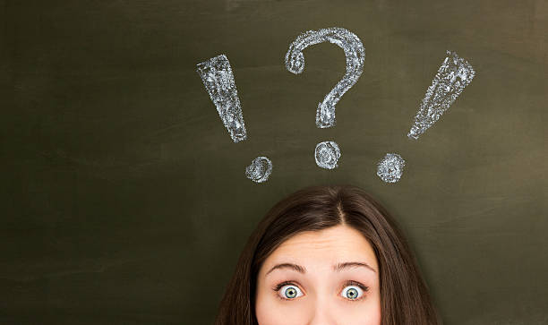 Thinking young woman with question mark on blackboard Thinking young woman with question mark on blackboard. raised eyebrows stock pictures, royalty-free photos & images