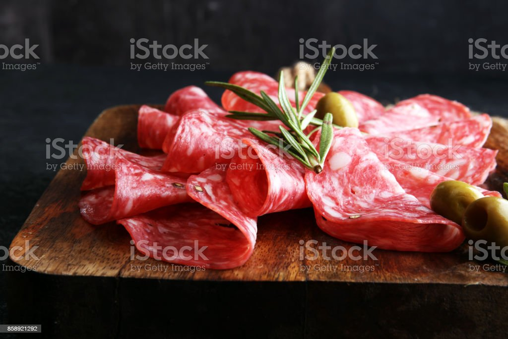 thinly sliced salami on a wooden cuttingboard stock photo