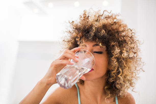 thirsty african american woman drinking water. - drinking water stock photos and pictures