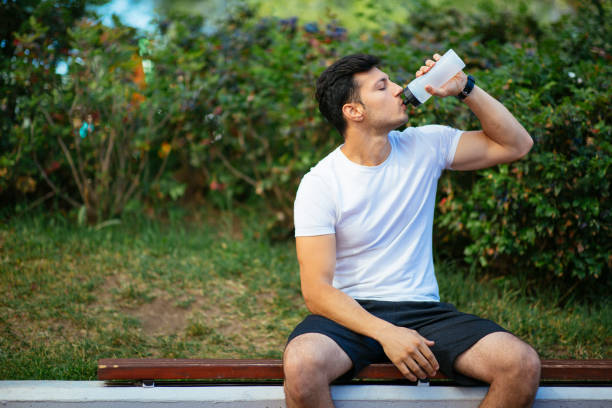 Thirsty athlete drinking water after training stock photo