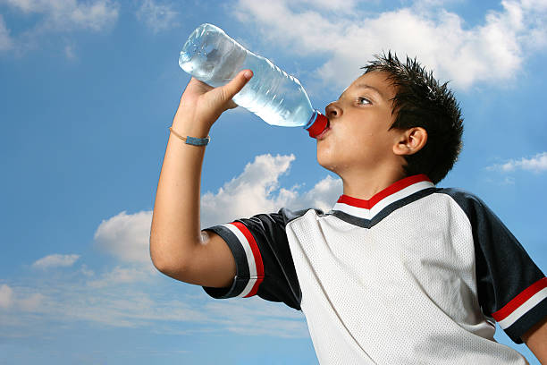 Thirsty boy drinking water outdoors stock photo