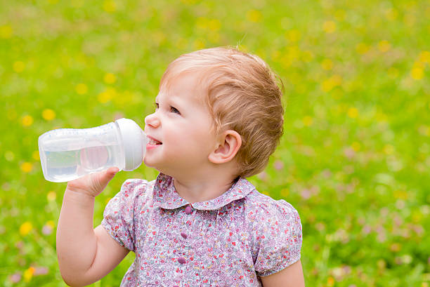 Thirsty Cute baby drinking water from bottle outside stock photo