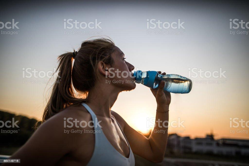 Thirsty female athlete drinking fresh water at sunset. royalty-free stock photo