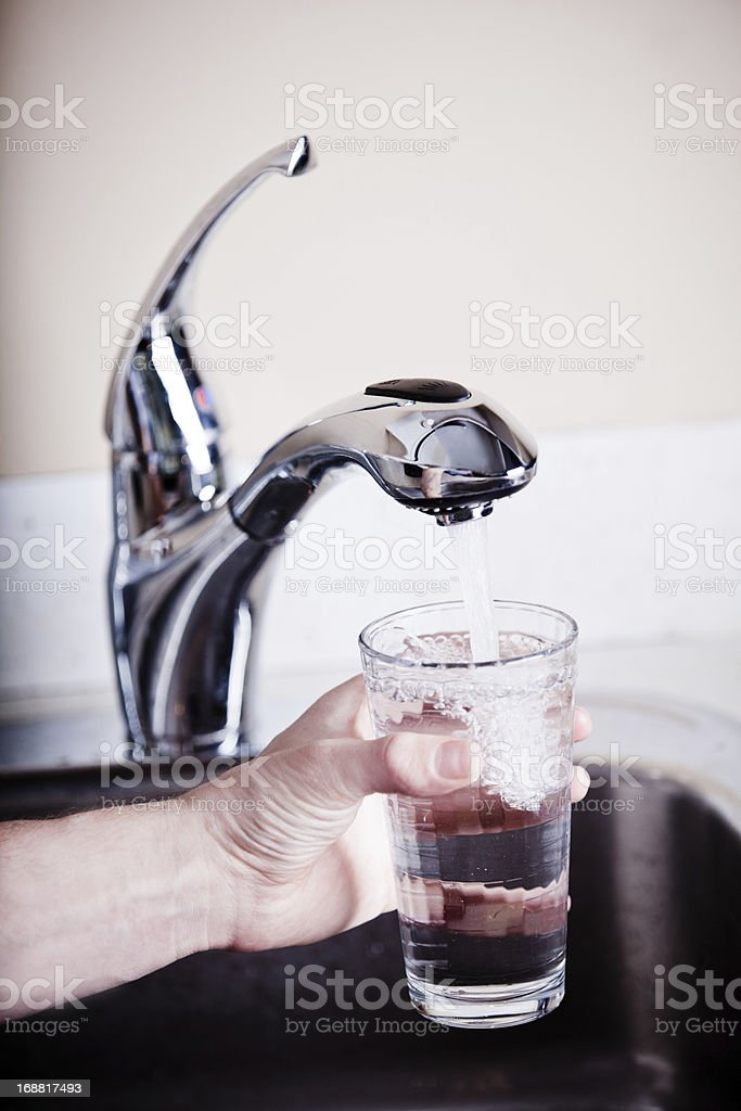 Thirsty man filling a big glass of water stock photo