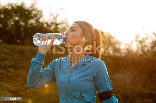 Young athletic woman drinking water with her eyes closed while having water break during morning run in nature.
