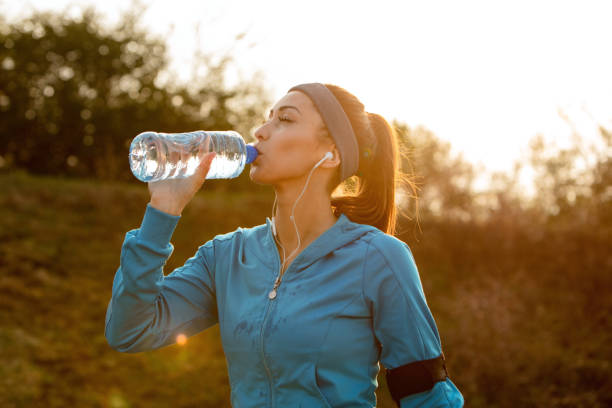 Thirsty runner refreshing herself with water while jogging in the morning. Young athletic woman drinking water with her eyes closed while having water break during morning run in nature. groyne stock pictures, royalty-free photos & images