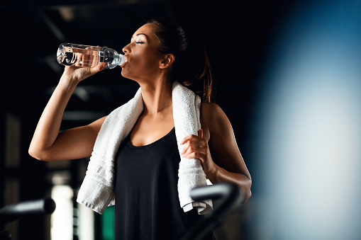 Young athletic woman refreshing herself after working out in a gym and drinking water with her eyes closed. Copy space.