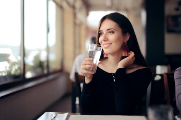 Durstige Frau trinkt ein Glas Wasser in einem Restaurant – Foto