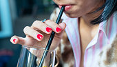 Thirsty woman drinking with straw