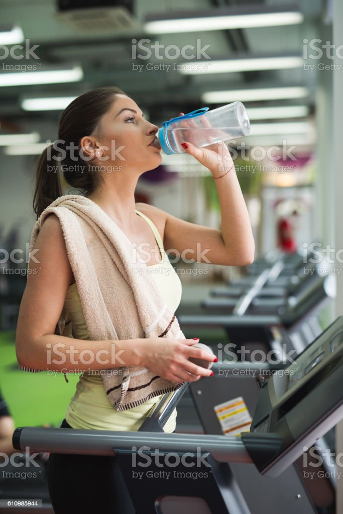 Thirsty woman in a gym drinking water from a bottle stock photo thirsty woman in a gym drinking water from a bottle royalty free stock photo sciox Gallery
