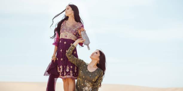 Thirsty women traveling in desert. Lost in desert durind sandshtorm stock photo