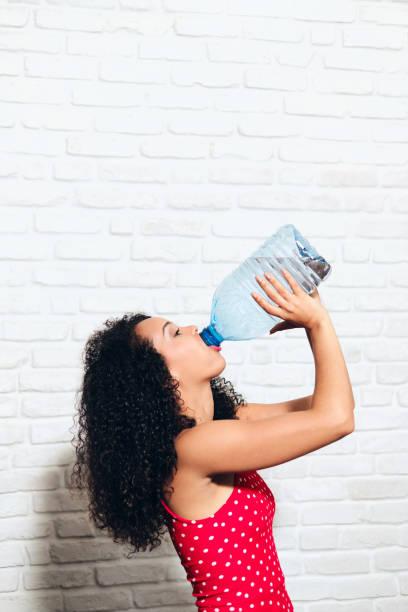 Durstiges Trinkwasser für junge Frauen aus Plastikflasche für die Gesundheit – Foto