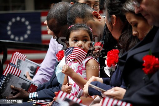 Philadelphia, PA, USA - June 14, 2019: The daughter of a immigrant holds an American flag while she joins her mother's naturalization ceremony on Flag Day at the historic Betsy Ross House in Philadelphia, Pennsylvania.