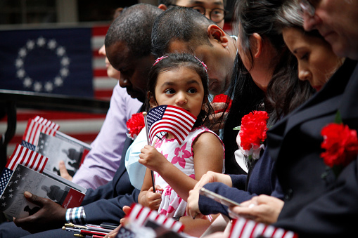 Philadelphia, PA, USA - June 14, 2019: The daughter of a immigrant holds an American flag while she joins her mother's naturalization ceremony on Flag Day at the historic Betsy Ross House in Philadelphia, Pennsylvania.\