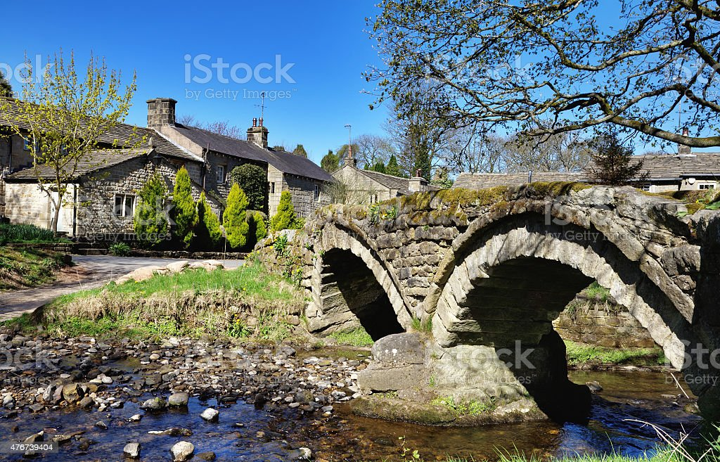 Thirteenth century packhorse bridge and the village of Wycoller stock photo