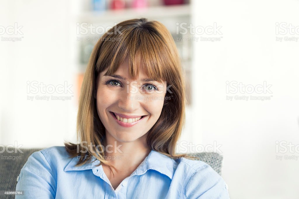 Thirty-year-old natural woman seated in modern home. Looking camera stock photo