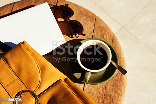 High angle shot of a cup of coffee and a bag neatly arranged on a coffee table during the day