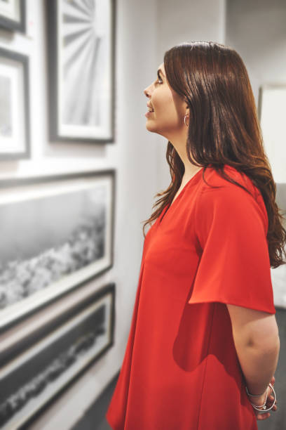 This art piece is phenomenal Shot of an attractive young woman looking at a painting at an art gallery critic stock pictures, royalty-free photos & images