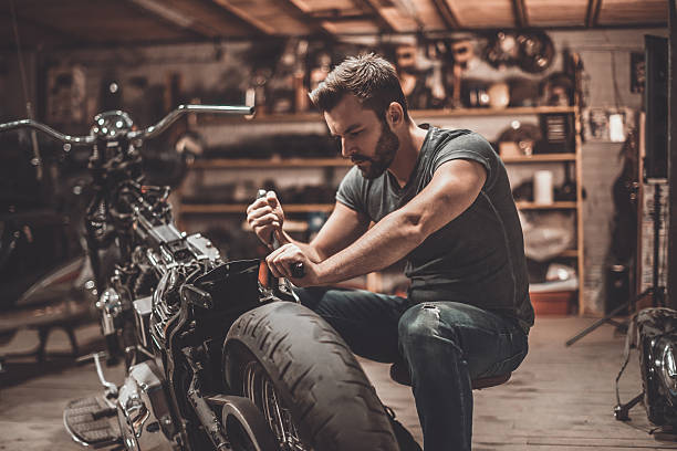 This bike will be perfect. Confident young man repairing motorcycle in repair shop hobbies stock pictures, royalty-free photos & images