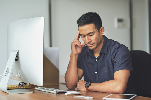 Shot of stressed young man sitting at his desk in his office