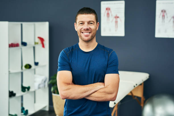 This career is the definition of fulfilling Cropped portrait of a handsome male physiotherapist standing with his arms folded in his office osteopathy stock pictures, royalty-free photos & images