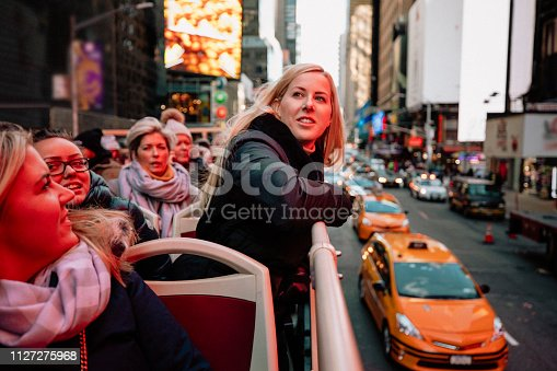A front-view shot of a group of women on a open top bus tour in New York City, they are sightseeing and having fun together, they are wearing warm clothing.