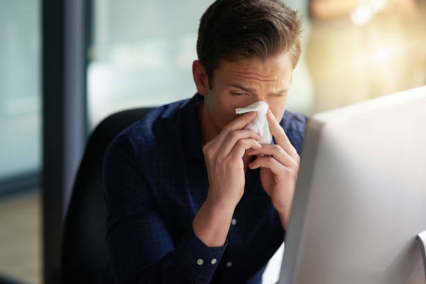 This cold is starting to torture me Shot of a young businessman blowing his nose in an office cold virus stock pictures, royalty-free photos & images