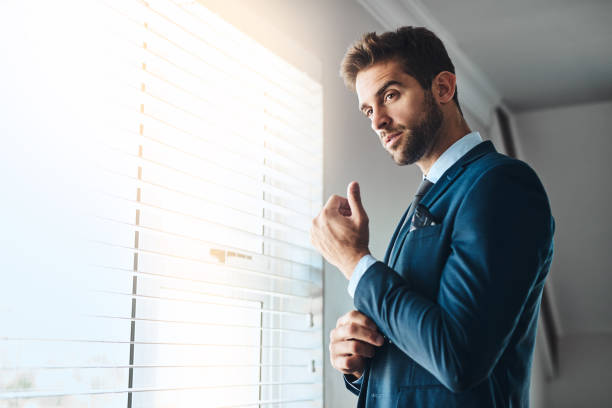 This completes the look Cropped shot of a handsome young man fastening his cuffs in his bedroom at home bachelor stock pictures, royalty-free photos & images