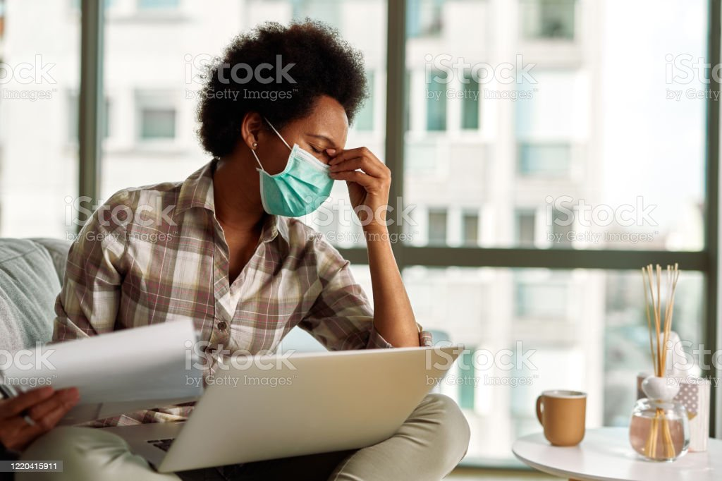 This constant work from home is so stressful! African American woman with face mask having a headache while going through paperwork and using laptop while working at home. Accidents and Disasters Stock Photo