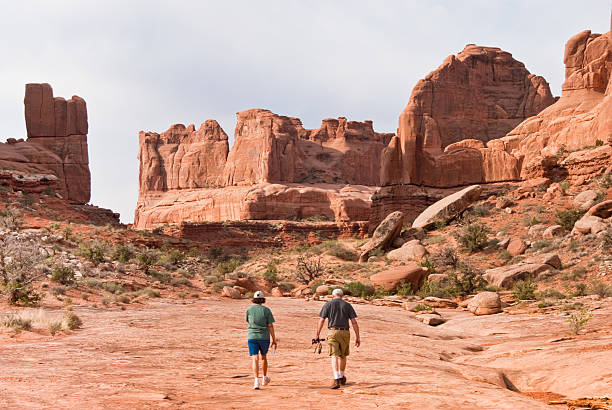 Hiking in Park Avenue Arches National Park, Utah, USA - May 16, 2012: This couple is hiking on the Park Avenue Trail. navajo sandstone formations stock pictures, royalty-free photos & images