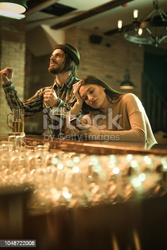 Young woman feeling bored and using cell phone while her boyfriend is watching a sports game in a bar.