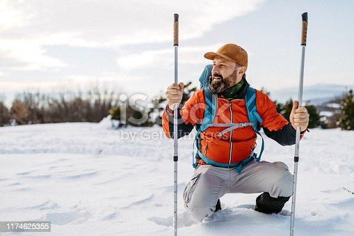 Man with hiking poles walking through snow on mountain peak
