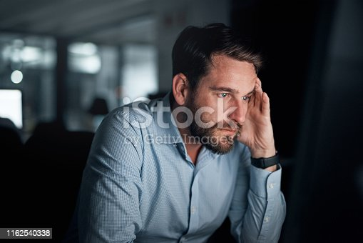 Shot of a young businessman looking frustrated while working on a computer in an office at night
