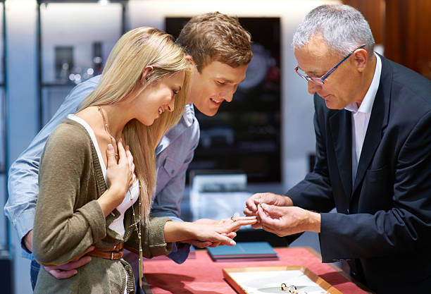 This decision will last a lifetime Happy young couple trying on engagement rings in a jewelery store jeweller stock pictures, royalty-free photos & images