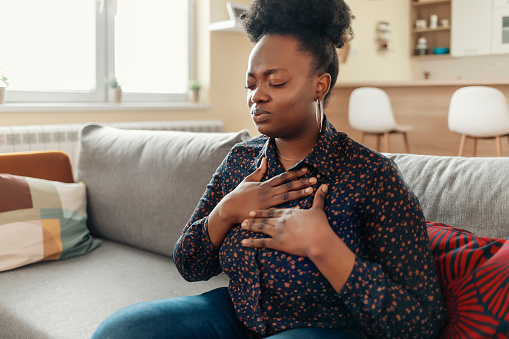 Pressure in the Chest. Close-up Photo of a Stressed Obese African American Woman Who Is Suffering From a Chest Pain and Touching Her Heart Area.