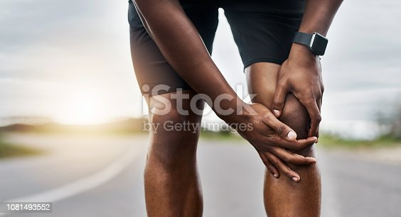Closeup shot of a sporty man suffering with knee pain while exercising outdoors